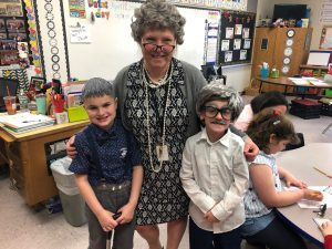 "adult and two students dressed up in ""old folks"" clothing"