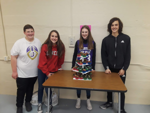 four students standing behind a table with a cupcake display