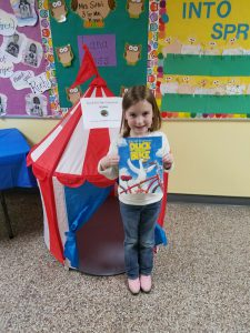 student by a small striped pop-up play tent