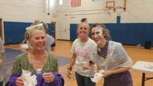 staff members covered in whipped cream