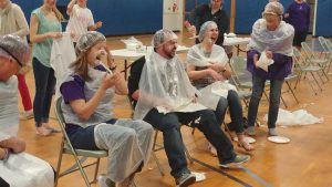staff members covered in plastic ponchos and whipped cream pies
