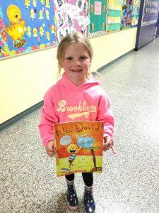 little girl holding book she won