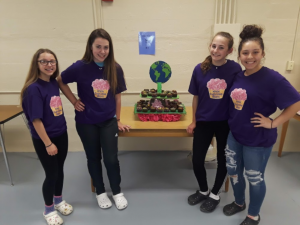 four students with cupcakes on shirts holding a display of cupcakes