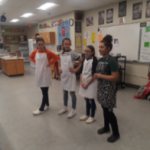 four students, three wearing aprons