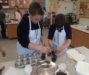 two students putting batter in cupcake tins