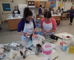 two students decorating cupcakes