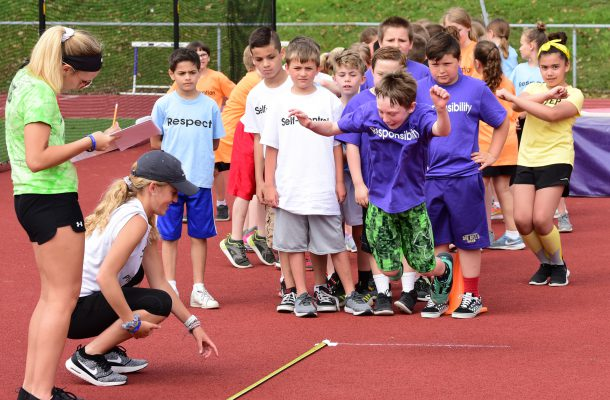 """adult places measuring tape on ground while students line up to """"long jump"""""""