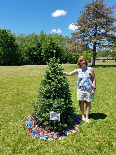 Mrs. Quinn standing next to small pine tree