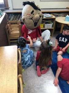 Mojo seated on floor with students