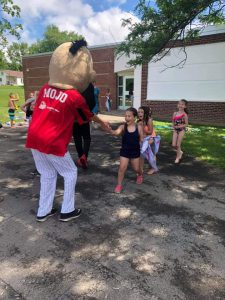 Mojo the Mascot shaking hands with students