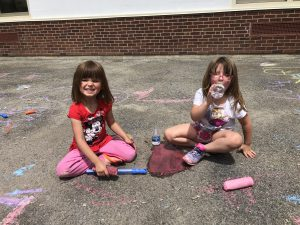two girls sit on a paved surface decorated with chalk