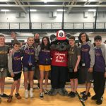 eight teens pose with the Odyssey of the Mind mascot, a raccoon in a red t-shirt and red and white ball cap