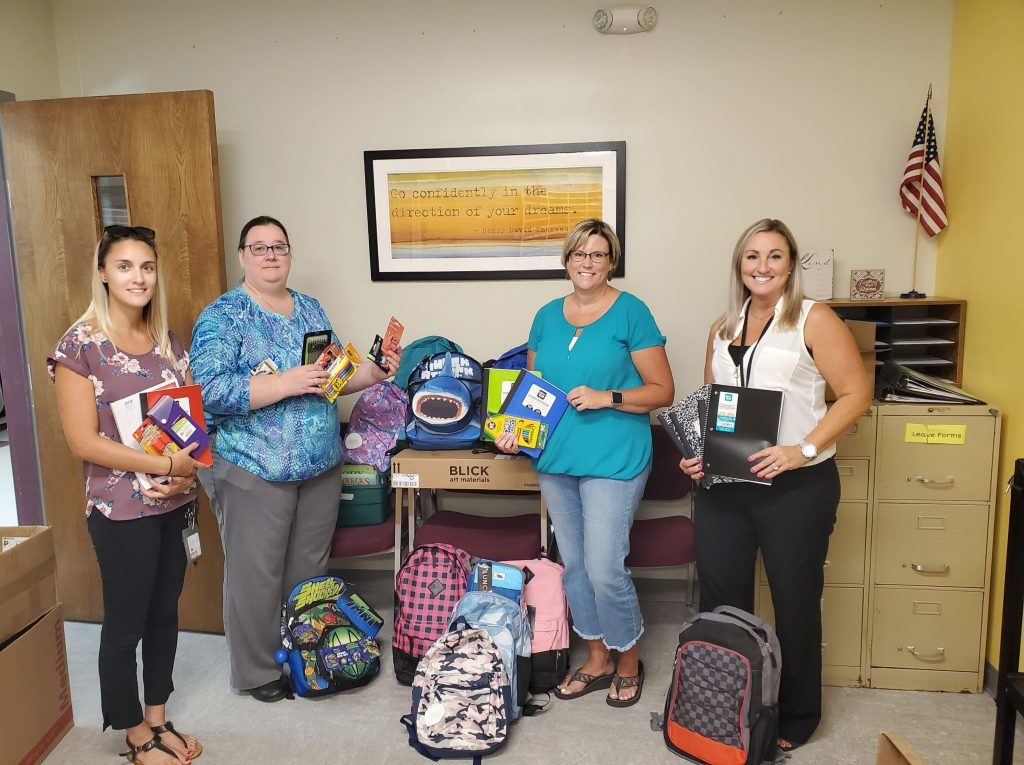 four staff members stand with backpacks and donated supplies