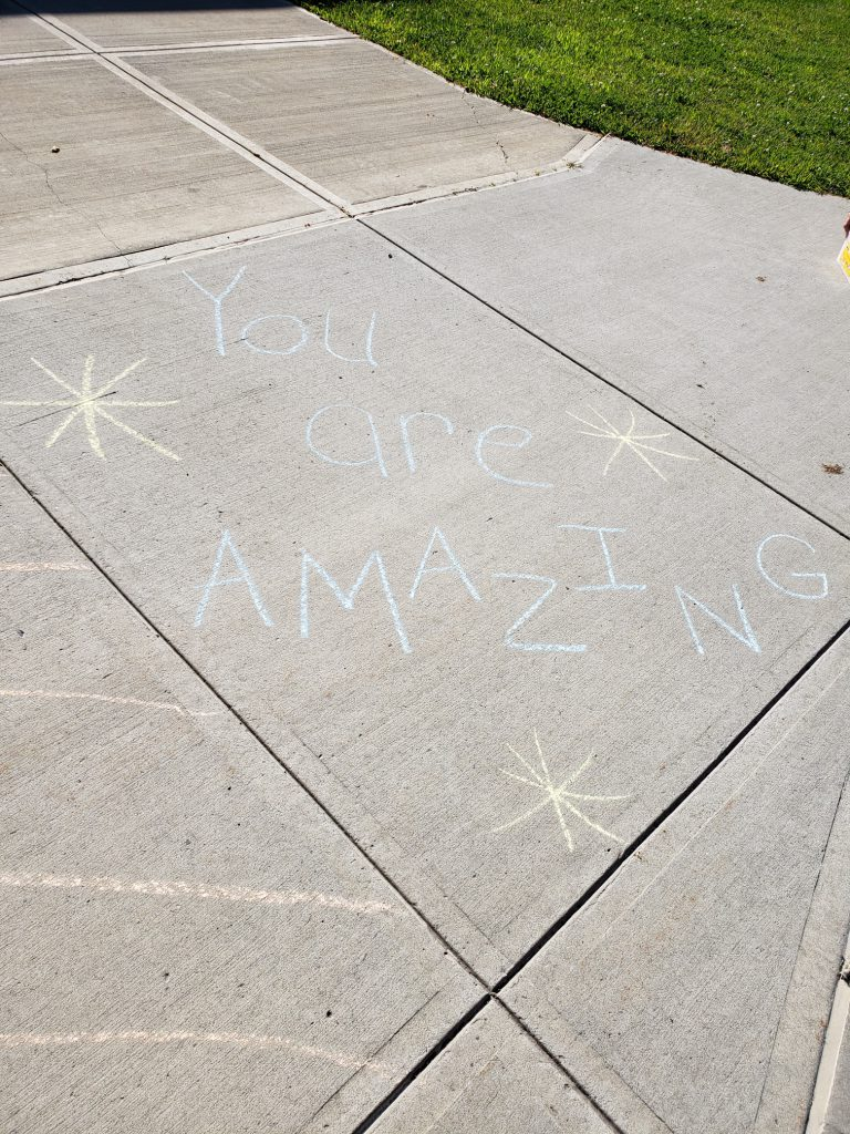 """you are amazing"" written on sidewalk in chalk"