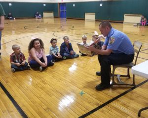 Firefighter Duesler reading to children in gymnasium