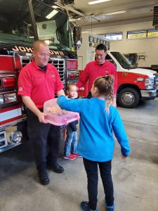 firefighter holds tray while student picks item off of it