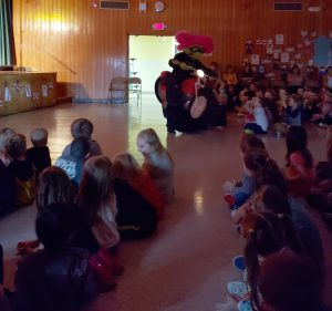 students are seated on the floor during the performance