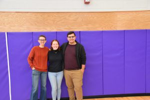 three students posing against wall