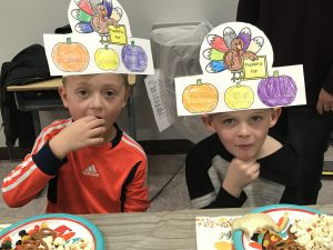 two students wearing headdresses colored with fruits and veggies
