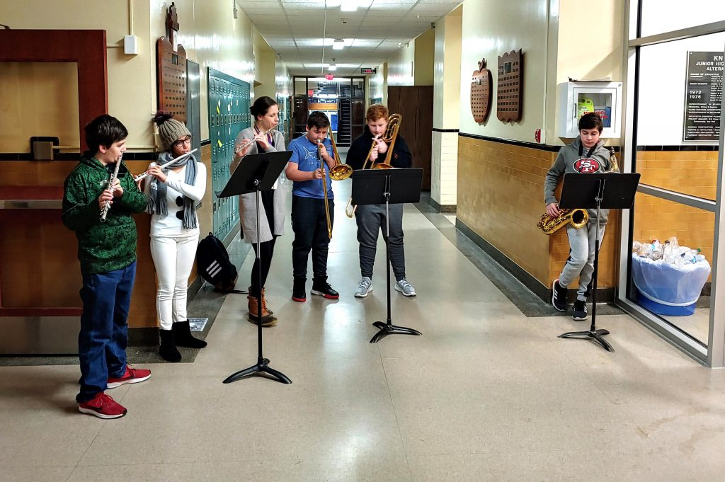 five students and one teacher playing musical instruments inside Knox entry way
