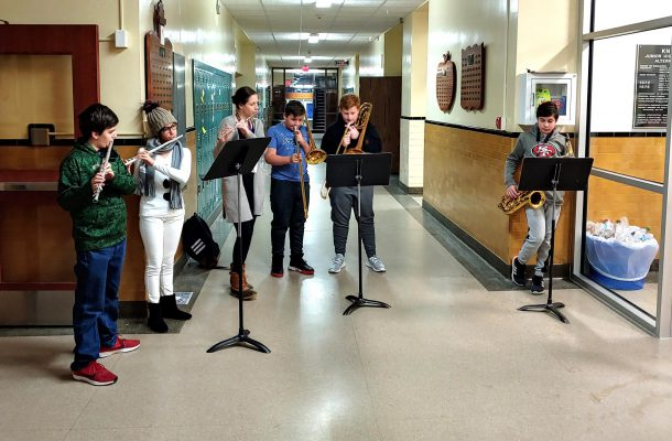 six students playing musical instruments inside Knox entry way