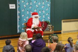 santa sitting in front of a snowman backdrop, reading a book to students