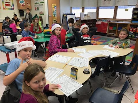 students in santa hats seated at a table