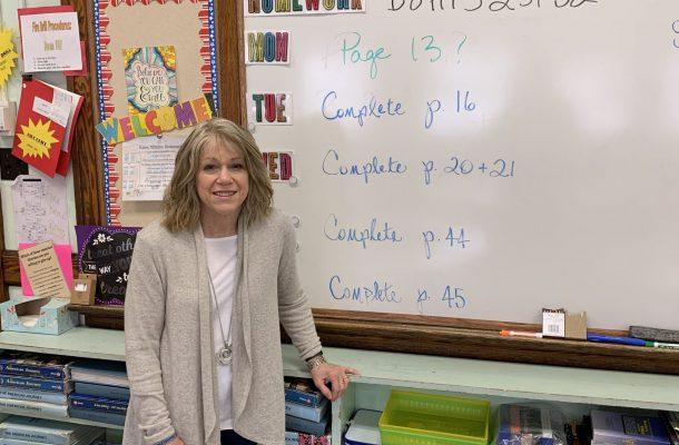 Mrs. Bruno next to classroom whiteboard