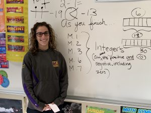Quinn Swartwout next to classroom whiteboard