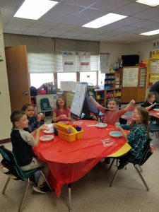 students at table display their creations