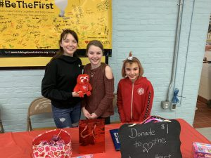 three students standing together, one holding a red stuffed animal