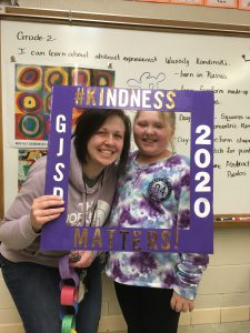 adult and child pose inside picture frame labeled GJSD Kindness 2020