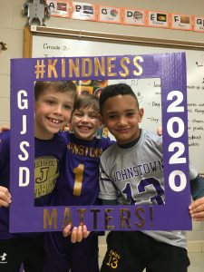 "three students peek through a kindness challenge ""photo frame"""