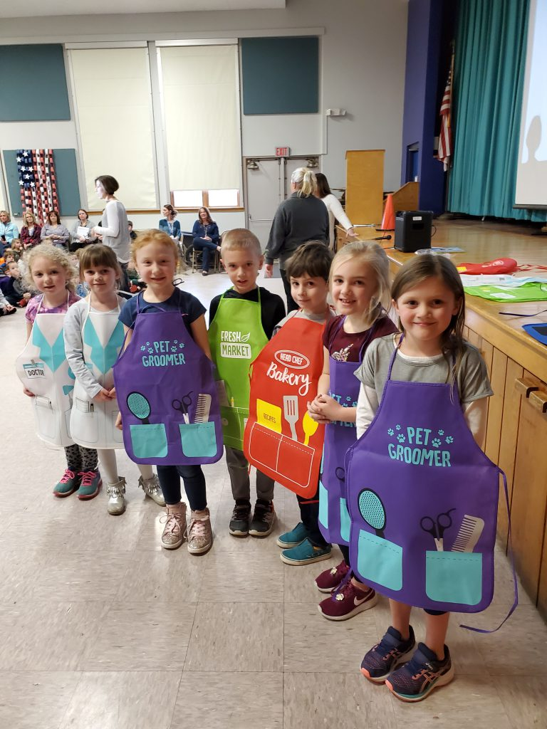 students wearing aprons stand by stage at Pleasant Ave