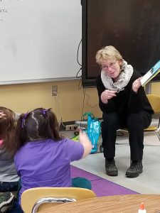 retired teacher reading to students
