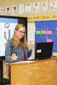 Kindergarten teacher Katie Warner holds up a flashcard to her remote students.