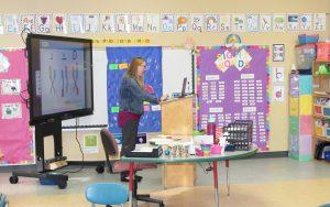 Kindergarten teacher Katie Warner is shown teaching a remote classroom into a computer, from her empty classroom.