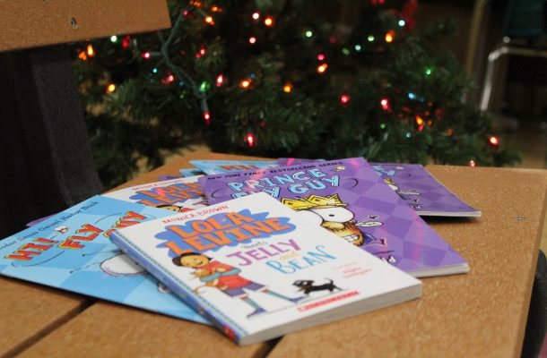 """Donated books are on display on the Warren Street Elementary """"Buddy Bench,"""" with a Christmas tree with colored lights shown in the background."""