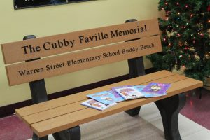 "Donated books are on display on the Warren Street Elementary ""Buddy Bench,"" with a lighted Christmas tree in the background."