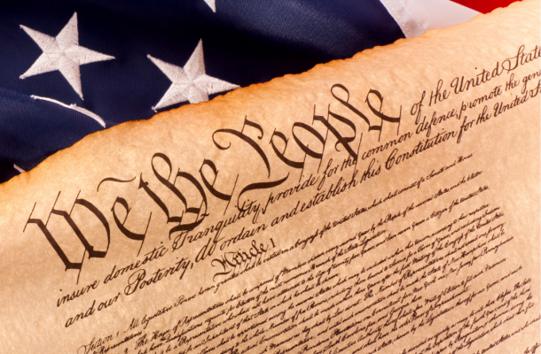 A picture of the Constitution is shown with an American flag.