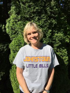 Laura Lakata, a Teaching Assistant at Warren Street Elementary School, is shown wearing a little bills t-shirt, standing outside in front of a shrub, and smiling.