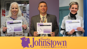 three people are shown holding up ABC Award certificates, with the Johnstown distirict logo below them.