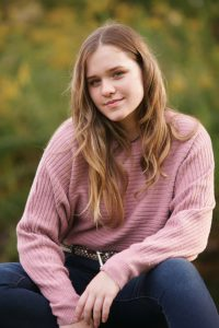 a young lady wearing a pink sweater and jeans sits outside smiling at the camera.