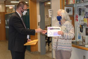 a man wearing a dark suit and white face masks hands an award and certificate to a woman with white hair and a blue mask.