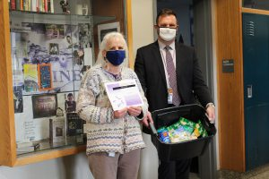 a woman with white hair and a blue mask is shown holding a certificate next to a man dressed in a dark suit with a white mask, holding a plastic bin full of non perishable foods.