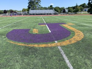 an oversized letter J in purple and gold is shown at the 50 yard line of the knox athletic field.