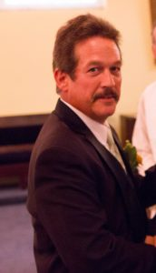 a man with dark hair and a mustache is shown wearing a suit and tie and smiling to the camera