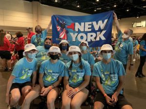 """9 students wearing blue shirts, white hats and face masks pose in front of a sign that reads """"New York"""""""