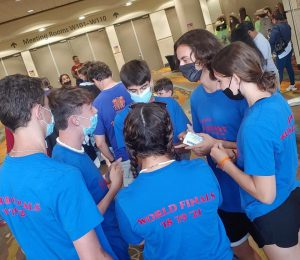team members wearing blue shirts and face masks huddle together to strategize