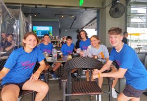 team members wearing blue t-shirts and sitting at a lunch table, turn to smile at the camera